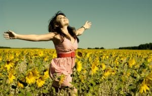 woman with her arms open in sunflower field