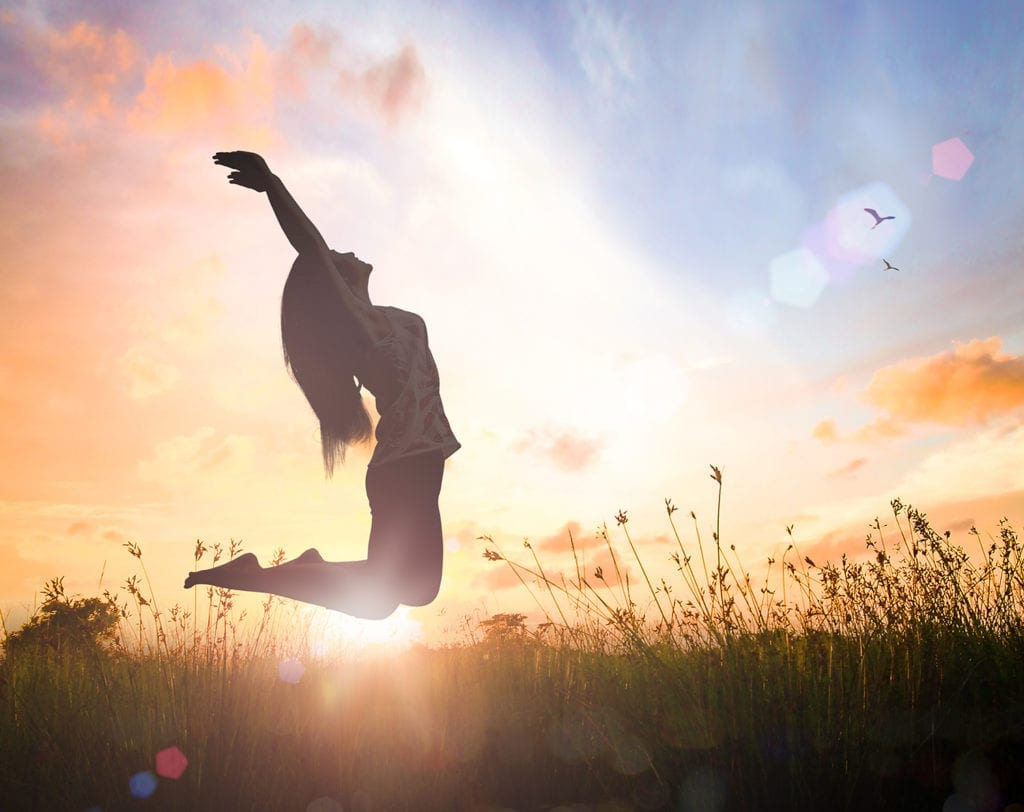 Woman jumping in grass field with sunshine