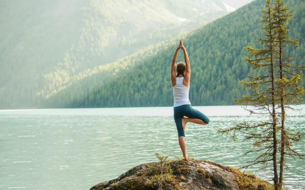 Woman doing Yoga by a mountain lake